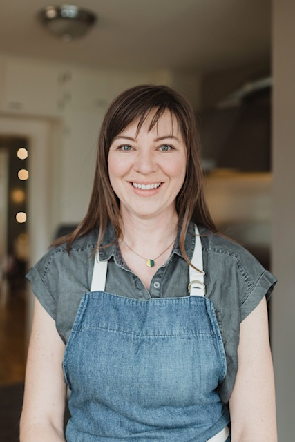 Leah Van Tassel in an apron smiling at the camera